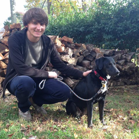 Oliver petting Sapphie the dog next to a pile of firewood