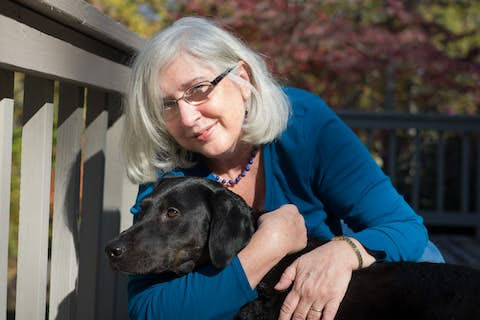 a portrait of Cathy Flanagan hugging Sapphie the dog closely