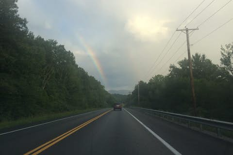 A rainbow on a rainy rural highway with green trees all around.