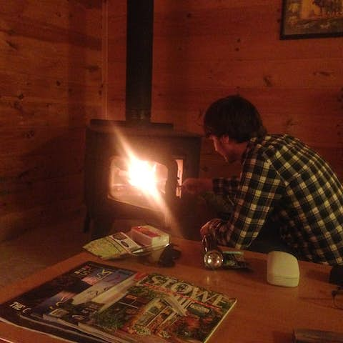 Oliver tending a fire in the cabin