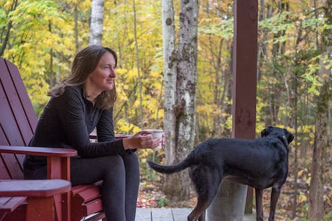 Jean drinking tea with Sapphie the dog on the deck of a cabin in the woods
