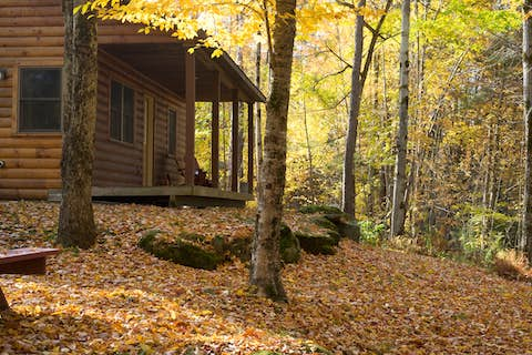 a cabin in a wooded area with a back porch and back yard
