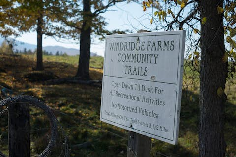 sign in a wooded area reading Windridge Farms Community Trails