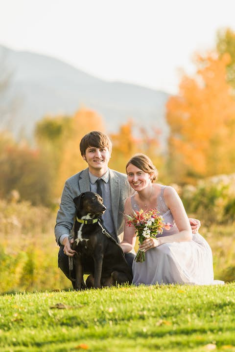 pre-wedding scene: Jean and Oliver crouching with Sapphie the dog with mountains and trees in the background