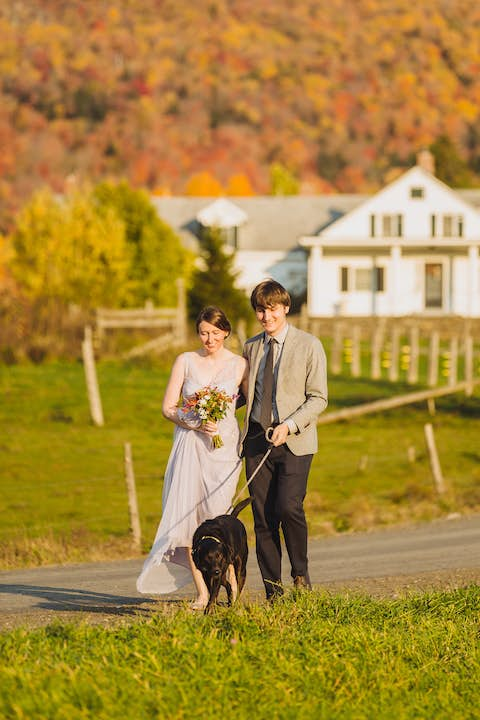 pre-wedding scene: Jean and Oliver walking with Sapphie the dog on a road near an old farm house