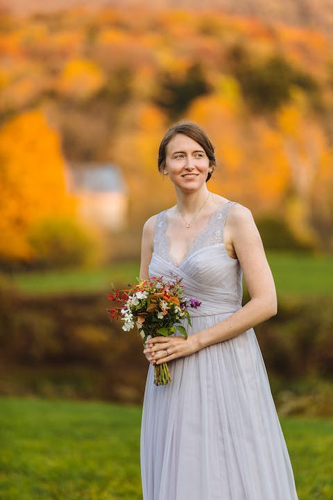 portrait of Jean wearing pale lilac dress holding a bouquet with orange fall leaves in the background