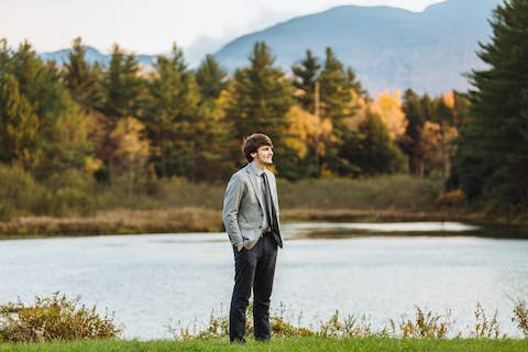 wide shot of Oliver dressed in a grey jacket and blue pants standing in front of Sterling Pond with mountain view