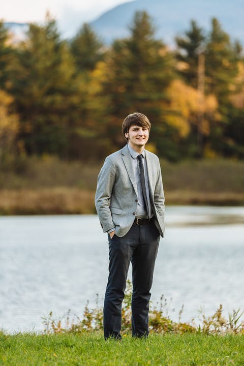 portrait of Oliver dressed in a grey jacket and blue pants standing in front of Sterling Pond with mountain view