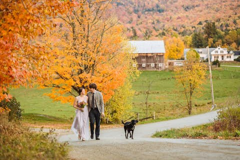 Oliver and Jean walking with Sapphie on a dirt road in front of orange maple leaves, with mountains and farm in the background