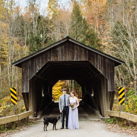 Oliver, Jean, and Sapphie the dog standing in front of an old wooden covered bridge
