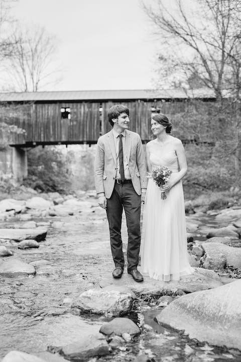 monochrome shot Jean and Oliver standing on a stone in the Brewster River with a covered bridge in the background