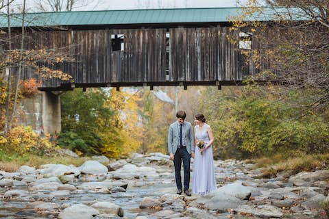 Jean and Oliver laughing and standing on a stone in the Brewster River with a covered bridge in the background