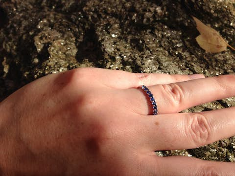 Jean's hand with sapphire and silver ring on a glinting rock