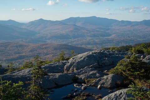 a view of mountains, including Mount Mansfield, from a bare rocky mountain top, with a pool of water in the background