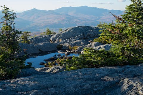 small pool of rain water in the rocks on top of Mount Hunger, reflecting blue sky