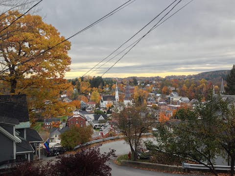 a view from the top of a road on a hill looking down on the roofs of buildings in the town of Montpelier with bright fall leaves