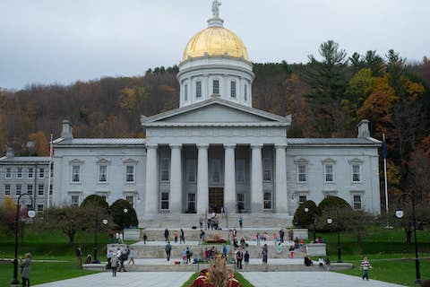 the Capitol building in Montpelier, with a white stone face and a gold dome, with late fall woods in the background
