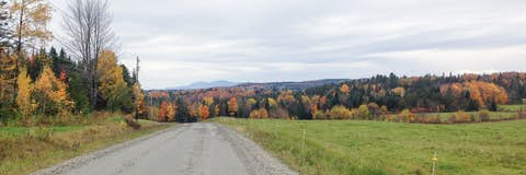 wide view of a dirt road near Greensboro, surrounded by farms, woods, and hills, with mountains and fall leaves in the background